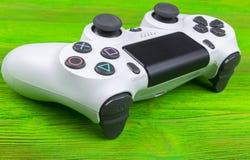 Console de jeu de Sony PlayStation 4 avec un dualshock 4 de manette sur la console verte de jeu vidéo à la maison de fond Image stock