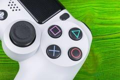 Console de jeu de Sony PlayStation 4 avec un dualshock 4 de manette sur la console verte de jeu vidéo à la maison de fond Images libres de droits