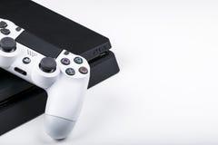 Console del gioco di Sony PlayStation 4 con un dualshock bianco 4 della leva di comando su fondo bianco, console del gioco di vid Immagini Stock Libere da Diritti