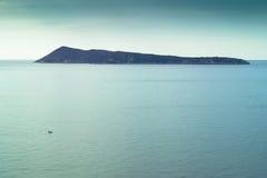 Console e barco de pesca pequeno no mar calmo Fotografia de Stock