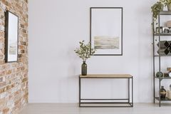 Console table with glass vase. Simple painting above wooden console table with twigs in a glass vase in modern living room interior royalty free stock images