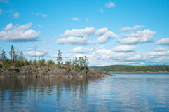 Consoles do norte da floresta em um lago enorme Fotografia de Stock