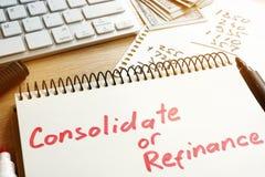 Consolidez ou refinancez manuscrit dans un bloc-notes images libres de droits