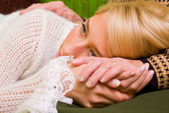Consoling. A young woman  laying her head on her grandmother's legs - part of a series Royalty Free Stock Photo