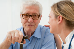 Consoling and care. Female nurse talking anda taking care of senior old men at hospital Royalty Free Stock Image