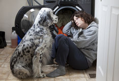 Consoling Friend. Woman crying on the floor while her dog tries to comfort her stock photo