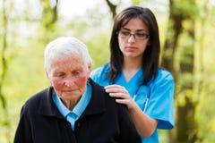 Consoling. Kind nurse in blue consoling sad senior patient stock photos