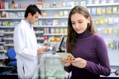 Consommateur avec la médecine à la pharmacie Image stock