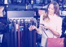 Consommateur choisissant les ceintures en cuir photographie stock