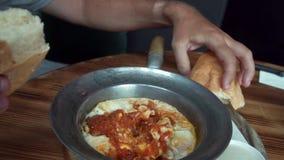Consommation avec les oeufs pochés de Shakshuka de mains avec la tomate et le pain servis dans une poêle Du Moyen-Orient arabe is banque de vidéos