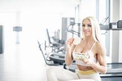 Consommation blonde de femme saine dans le gymnase image stock