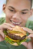 consommation d'hamburger de garçon d'adolescent Images libres de droits