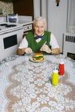 Consommation d'un hamburger Images stock