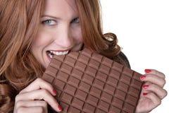 Consommation d'une grande barre de chocolat Photographie stock