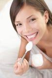 Consommation de femme de yaourt Photo stock