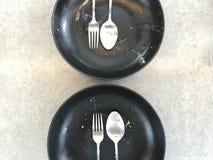 Consommation de finition de deux ensembles de cuillère inoxydable argentée, de fourchette et de plat en céramique noir Photos libres de droits