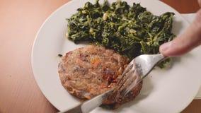 Consommation de la nourriture saine de végétarien ou de vegan, de la vraie aubergine et de l'hamburger végétal de carotte avec de clips vidéos