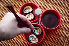 Consommation de Maki Sushi avec des baguettes Photos stock
