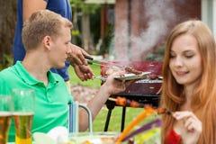 Consommation des casse-croûte sur un barbecue Photos libres de droits