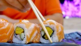 Consommation des petits pains de sushi dans un aliment de japans de restaurant Images libres de droits