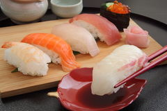 Consommation des sushi de dorade avec des baguettes, nourriture japonaise Photo stock