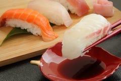 Consommation des sushi de dorade avec des baguettes, nourriture japonaise Photos libres de droits