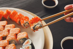 Consommation des sushi et des petits pains dans le restaurant japonais Photo libre de droits