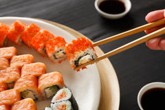 Consommation des sushi et des petits pains dans le restaurant japonais Photos stock