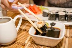 Consommation des sushi et des petits pains dans un restaurant japonais images stock