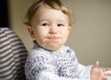 Consommation du bébé gai avec le visage malpropre Photo stock