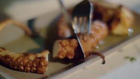 Consommation du plat de fruits de mer avec le poulpe banque de vidéos
