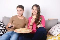 Consommation et montre TV de couples Image libre de droits