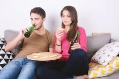 Consommation et montre TV de couples Photographie stock libre de droits
