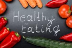 Consommation saine écrite parmi des légumes sur le tableau noir Image libre de droits