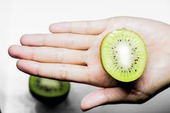 Consommation saine de kiwi et main humaine de sujet de régime jugeant un demi kiwi d'isolement sur un fond blanc dans le studio Photo libre de droits