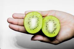 Consommation saine de kiwi et main humaine de sujet de régime jugeant un demi kiwi d'isolement sur un fond blanc dans le studio Photographie stock