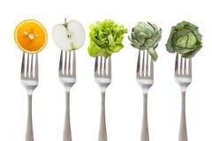 Consommation saine : fourchette du fer cinq avec des fruits et légumes, sur le blanc Photographie stock