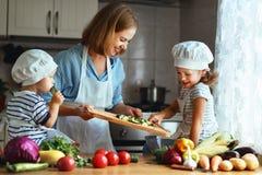 Consommation saine La mère et les enfants heureux de famille prépare le veget Images stock