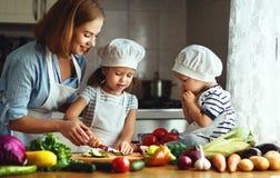 Consommation saine La mère et les enfants heureux de famille prépare le veget Photographie stock