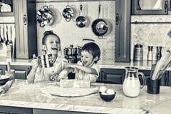 Consommation saine Les enfants heureux, prépare, fait cuire au four, des biscuits, concept de santé et d'amitié toujours série oc Images libres de droits