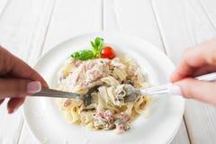 Consommation traditionnelle du carbonara de pâtes, mangeur POV photos stock