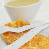 Consomme and french omelette. A bowl with consomme and a plate with a french omelette and a measuring tape, symbolizing the dieting concept Royalty Free Stock Photo