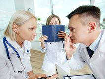 Conspiracy. Portrait of male clinician and his colleague conspiring with scared co-worker near by Stock Photos