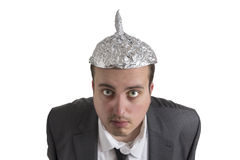 Conspiracy Freak with aluminum foil head. Distraught looking conspiracy believer in suit with aluminum foil head isolated on white background stock photos