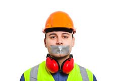 Conspiracy of silence. Young worker with insulating tape on his mouth preventing him from speaking Royalty Free Stock Images