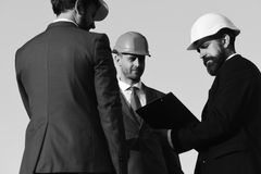Consrtuction concept. Leaders with beard and serious faces discuss project. Construction and business concept. Leaders with beard and serious faces discuss Stock Photos