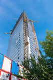 Consstruction site near Promenada mall in Bucharest. BUCHAREST, ROMANIA - SEPTEMBER 10, 2015 : Large cranes working on a skyscraper on construction site near Royalty Free Stock Image