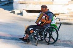 CONSTANTA RUMÄNIEN - AUGUSTI 21, 2010 gatamusiker i en rullstol som spelar dragspelet Arkivbilder