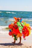 CONSTANTA RUMÄNIEN - AUGUSTI 21, 2010 leksaksäljare som går på stranden vid havet Royaltyfria Bilder