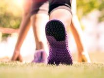 Constantes listos van Primer de zapatillas deportivas en hierba, señora joven en la posición de comienzo e ir a correr en parque foto de archivo